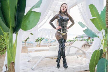 Mujer joven en ropa de látex al aire libre en la playa