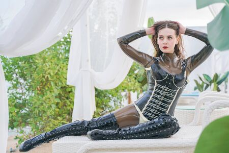 young woman in latex wear outdoor on the beach
