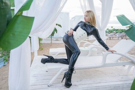 slim young blonde slavery girl in black latex catsuit with white corset