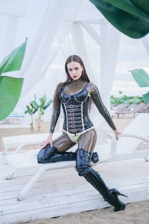 sexy young woman in erotic latex fetish wear outdoor on the beach