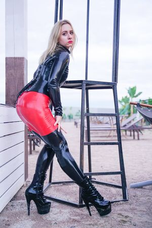 hot woman in black fashion rubber clothes in the evening on the beach