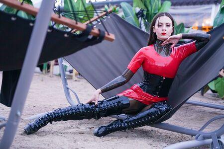 Mode stilvolle Dame trägt Latex-Gummi-Kleidung am Strand im Freien