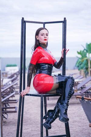 fashion stylish lady wear latex rubber clothes on the beach outdoor