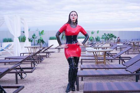 Mode stilvolle Dame trägt Latex-Gummi-Kleidung am Strand im Freien Standard-Bild