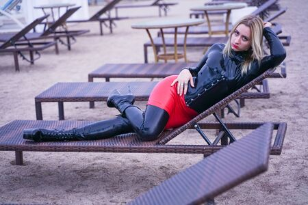 hot woman in black fashion rubber clothes in the evening on the beach Stock Photo