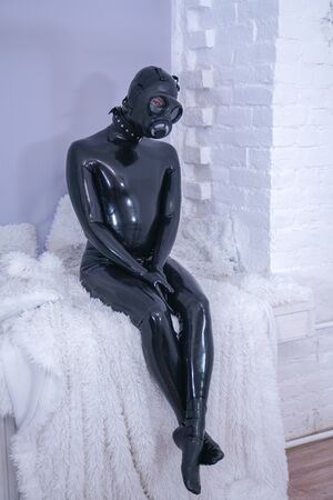 Man in the latex rubber black catsuit with gasmask 版權商用圖片