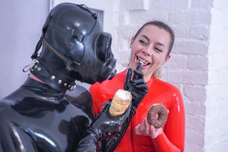 Happy lovers in latex catsuits having breakfast at home 版權商用圖片