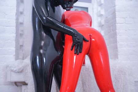 latex couple of woman in red catsuit and man in black overall with gasmask