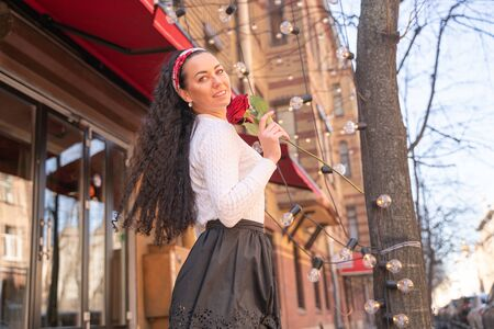 Young beautiful pretty girl with long hair with red rose in the city