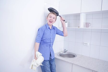 A cute teenager boy washing dishes at white kitchen alone