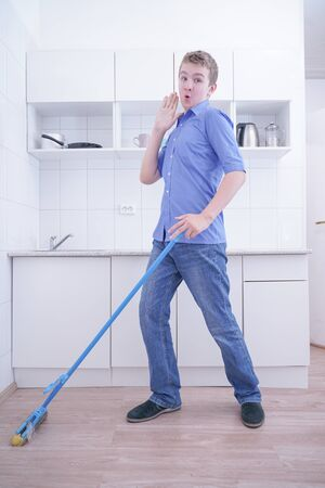 Teenager Boy Mopping The Floor and helps his parents to clean on kitchen Reklamní fotografie