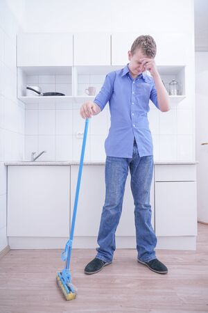 Teenager Boy Mopping The Floor and helps his parents to clean on kitchen Stock Photo