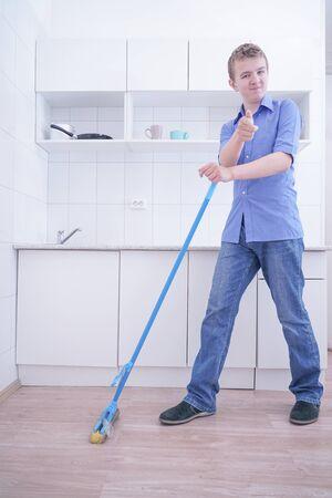 Muchacho adolescente trapear el suelo y ayuda a sus padres a limpiar en la cocina
