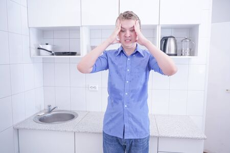 nice boy in blue shirt with emotions on kitchen alone