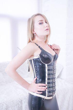 Belle maîtresse blonde vamp en corset noir sur fond de maison blanc