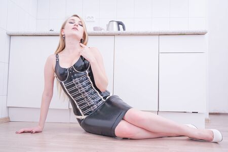 Beautiful blonde vamp mistress in black corset on white home background