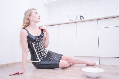 Beautiful sexy young woman with plate with milk on her kitchen alone