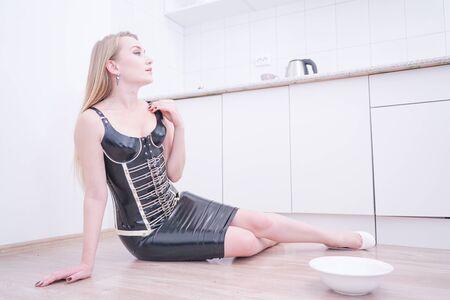 Belle jeune femme avec une assiette avec du lait sur sa cuisine seule