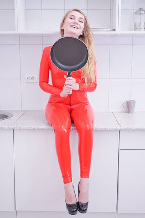 Woman beating with a frying pan on white kitchen background