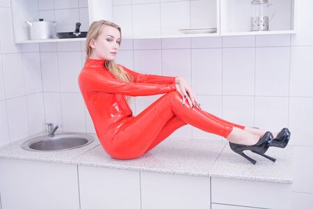 Beautiful woman in latex suit on a white home background Stock Photo
