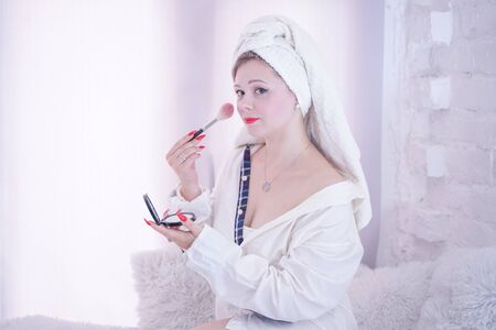 Woman with white towel on head do makeup sitting on windowsill Banco de Imagens
