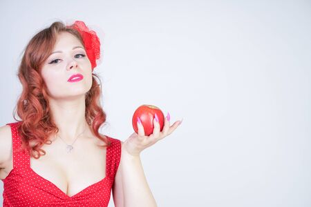 Sexy young pin-up girl holding red apple in her hand