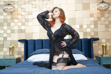 Young woman with black retro lingerie and nylon vintage stockings on bed