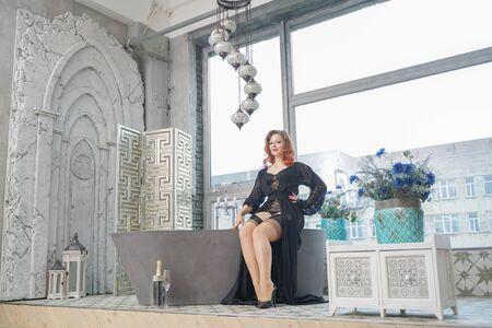 pin up woman on vintage bathtub in bathroom with big window