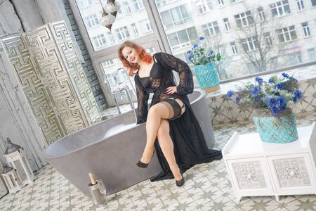 pin up woman on vintage bathtub in bathroom with big window