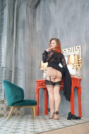 Chica pin up bastante retro cerca de la mesa de maquillaje en el vestidor Foto de archivo