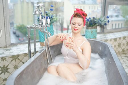 Seductive woman taking relaxing bath with champagne in her bath 版權商用圖片