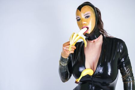 latex fetish plus size person with banana on white isolated studio background Standard-Bild