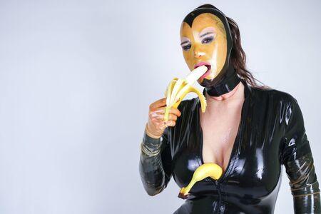 Latex Plus Size Person mit Banane auf weißem isoliertem Studiohintergrund