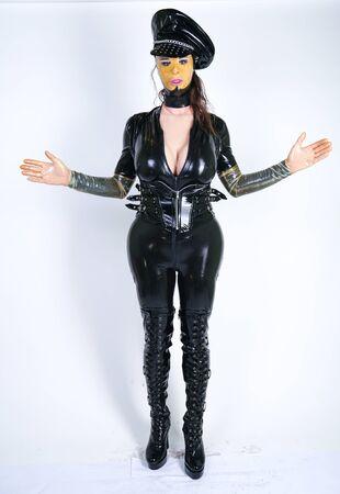 Latex plus Größe Person im Polizeipuppen-Outfit auf weißem isoliertem Studiohintergrund Standard-Bild