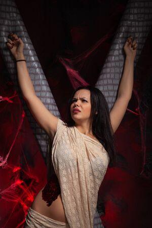Donna legata su sfondo scuro con sangue. Violenza sessuale, concetto di abuso.