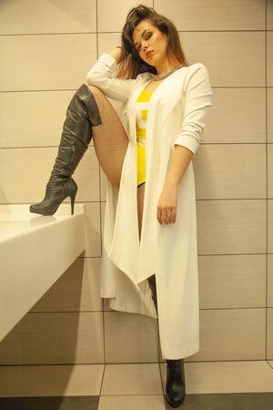 Chica guapa en el inodoro grande cerca del espejo solo