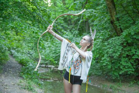 beautiful girl with american indian feathers holds bow and arrow