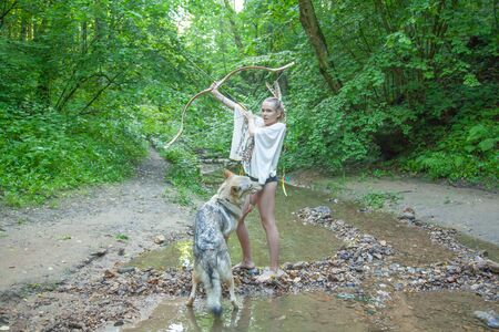 slim ethnic girl with her wolf dog in the deep forest alone