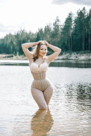 plus size vrouw met bochtige figuur in korset lingerie. Kaukasisch xxl mollig meisje wil zwemmen.