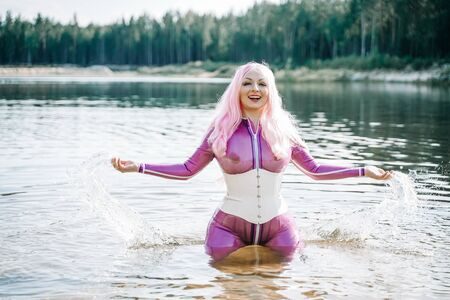 Sexy woman in transparent purple latex outfit posing in the water
