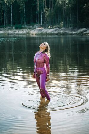 Femme sexy en tenue de latex violet transparent posant dans l'eau Banque d'images