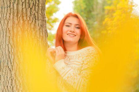 Retrato de primer plano al aire libre con hermosa mujer joven en suéter de otoño cálido cerca de hojas de otoño amarillas