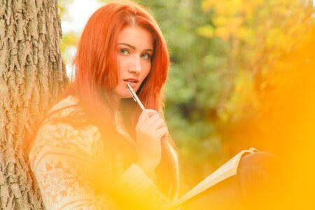 Beautiful young redhead woman in sweater walks in autumn