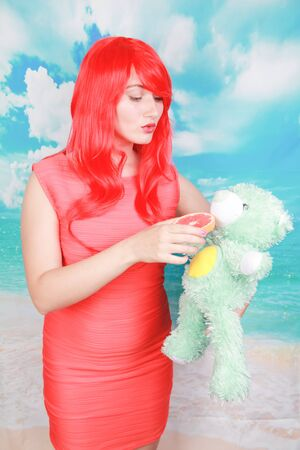 redheaded adult woman punish little cute teddy bear toy Standard-Bild