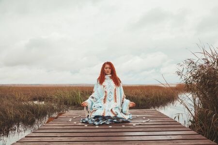 woman practices yoga and meditates with many candles near the autumn lake Stock fotó