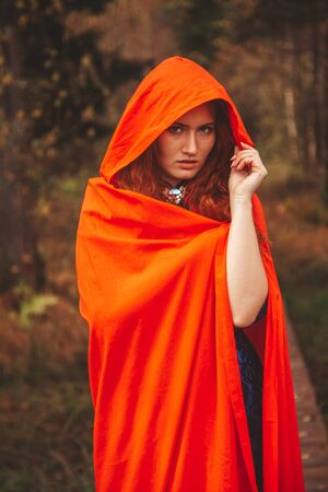 Pretty Red Riding Hood Woman is going on autumn forest road.