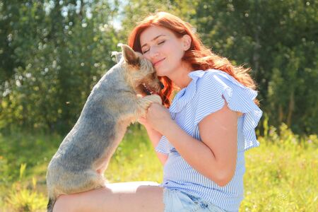 Cheerful pretty young woman sitting and hugging her dog on the nature