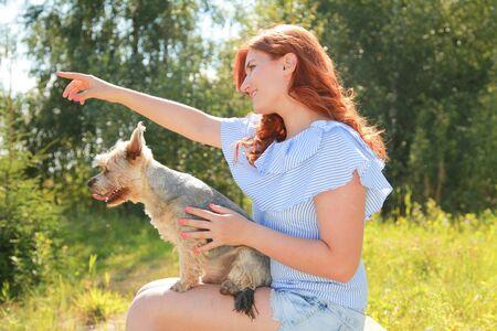 Joyeuse jolie jeune femme assise et serrant son chien dans la nature