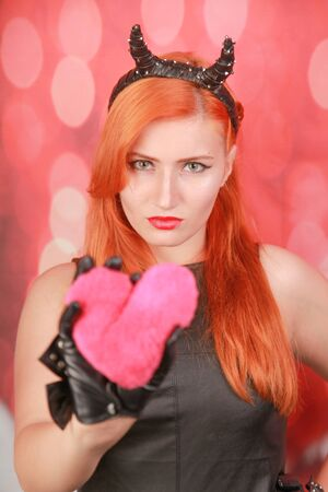 Devil girl with pink plush toy with heart shape on red background
