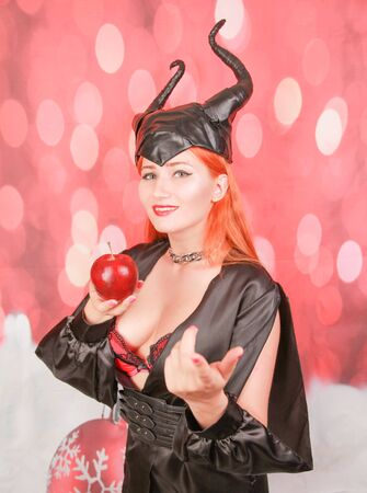 redheaded girl in black dress with devil horns holds red apple with temptation and seduction